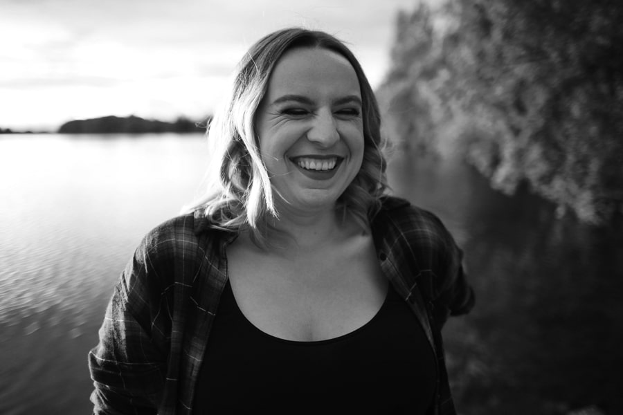 woman laughing by river black and white portrait