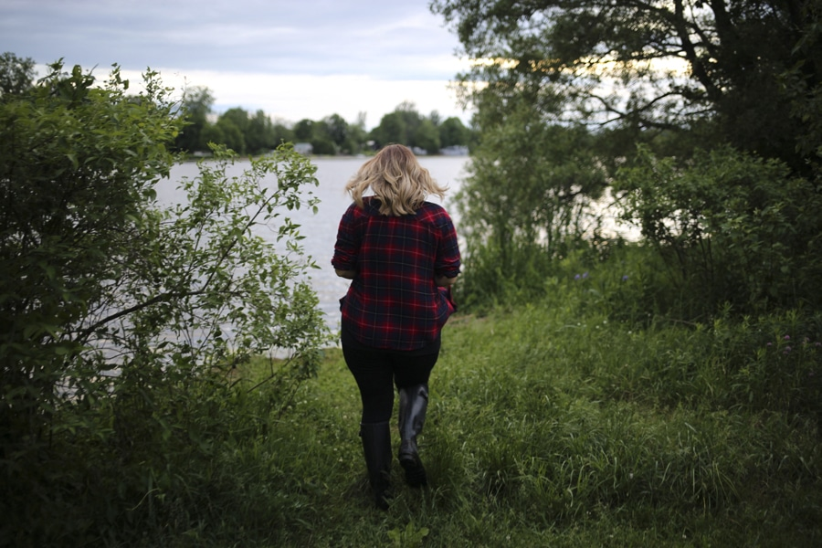 woman in plaid shirt walks towards river