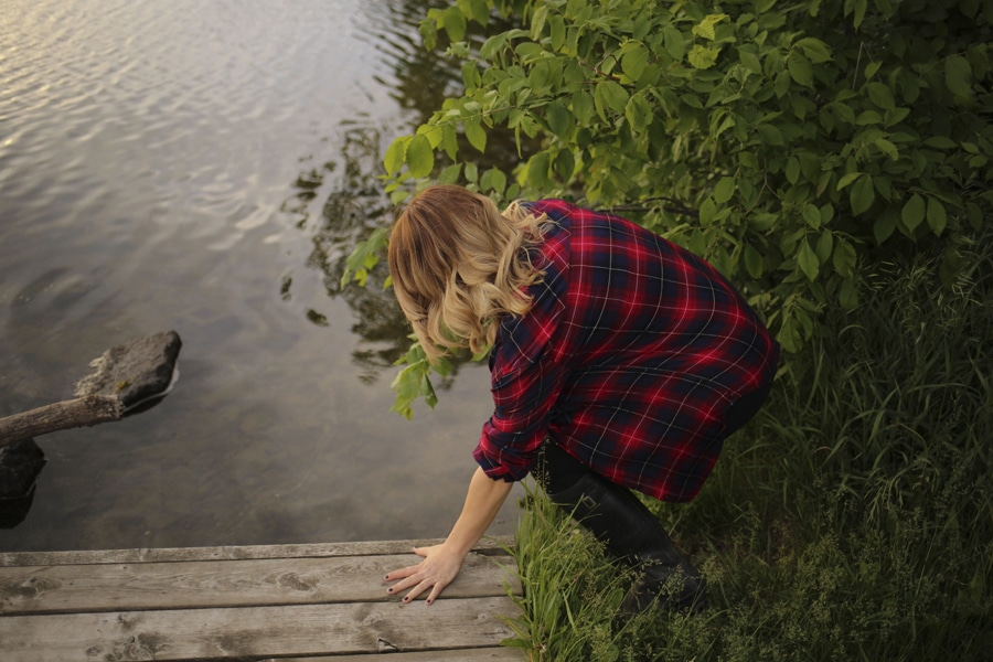 woman in plaid shirt steps into river