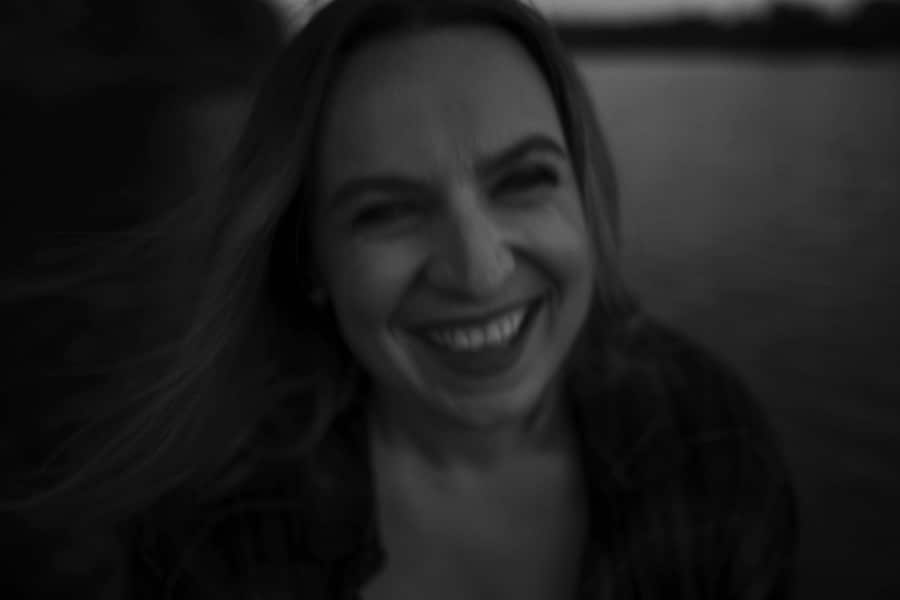 black and white portrait of woman laughing by water