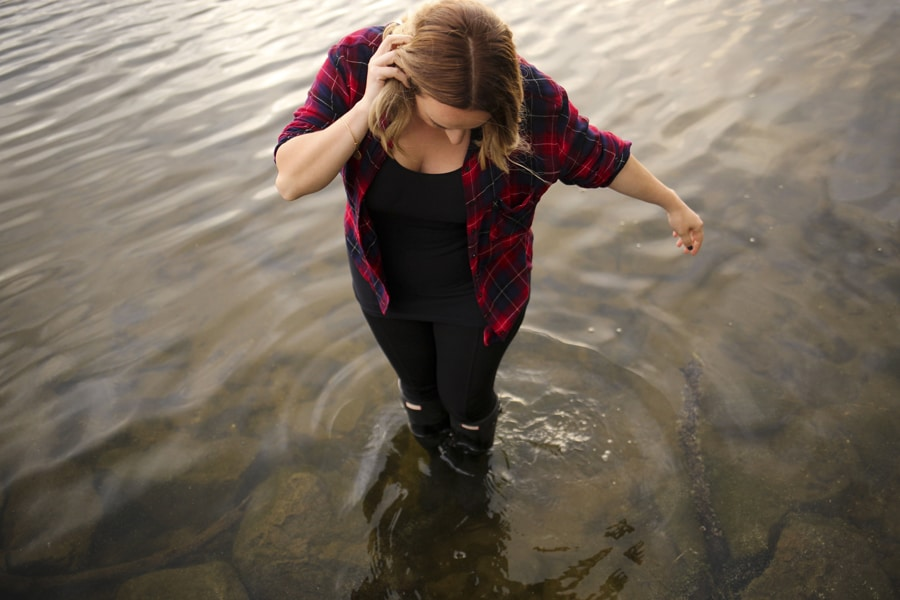 Woman in plaid shirt standing in river