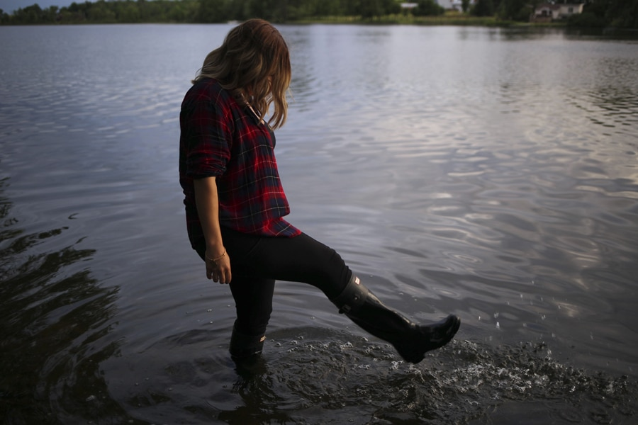 woman in rubber boots splashes in river