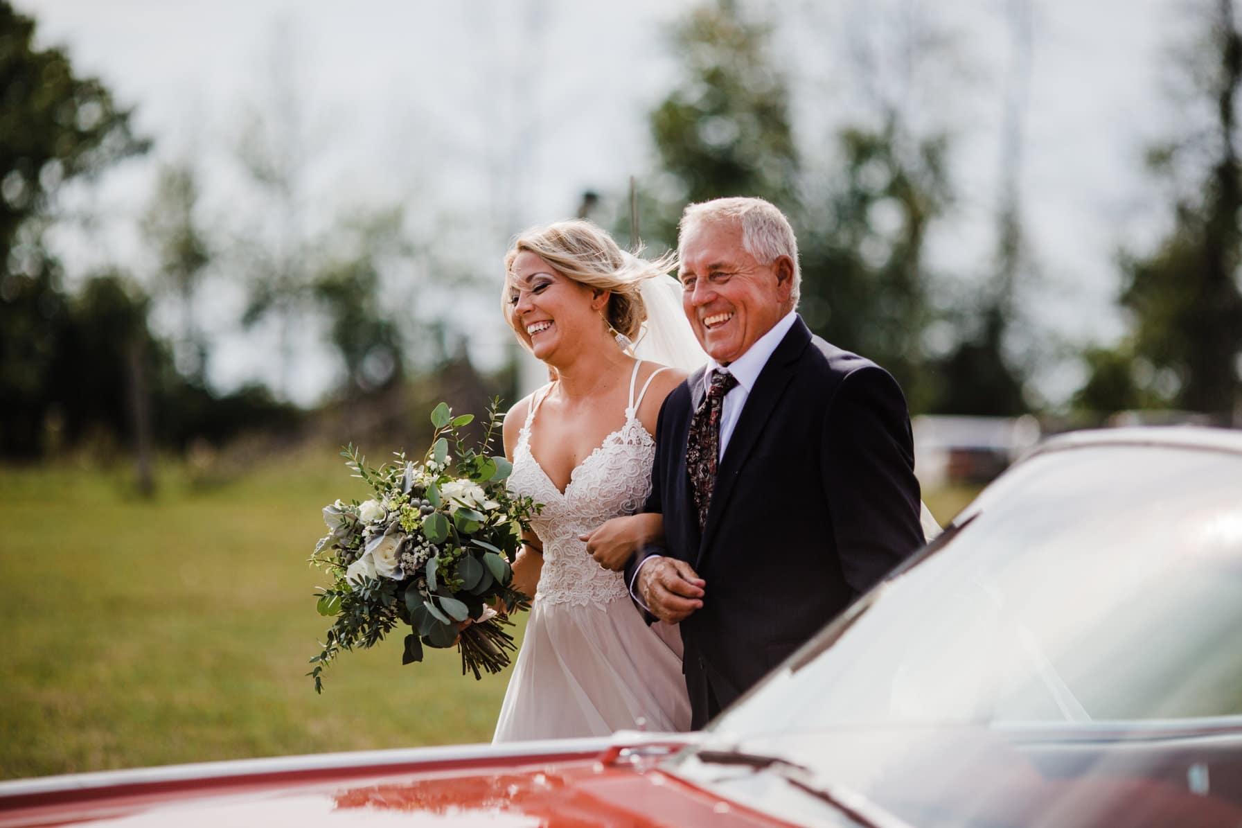 bride arrives with father - summer farm wedding