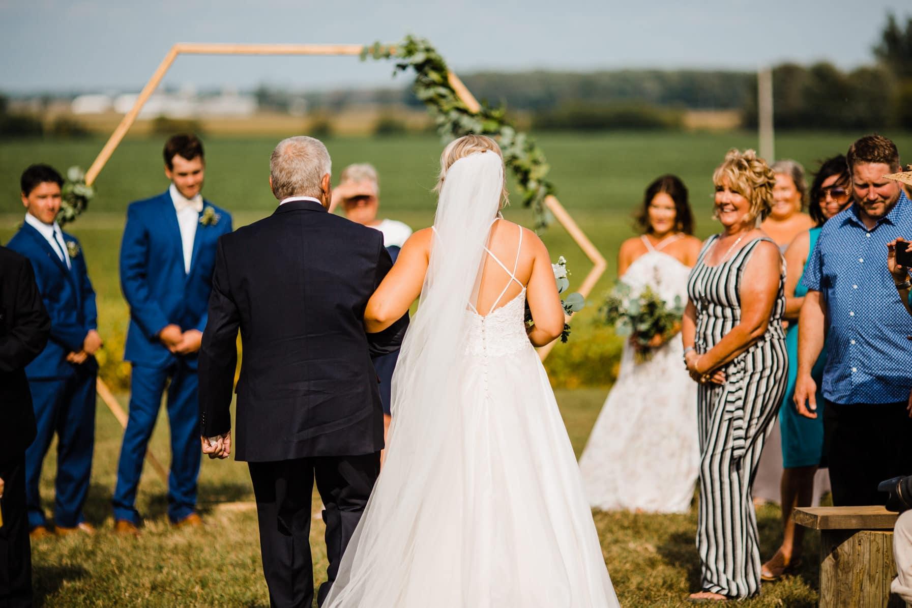 bride walks down the aisle - summer farm wedding