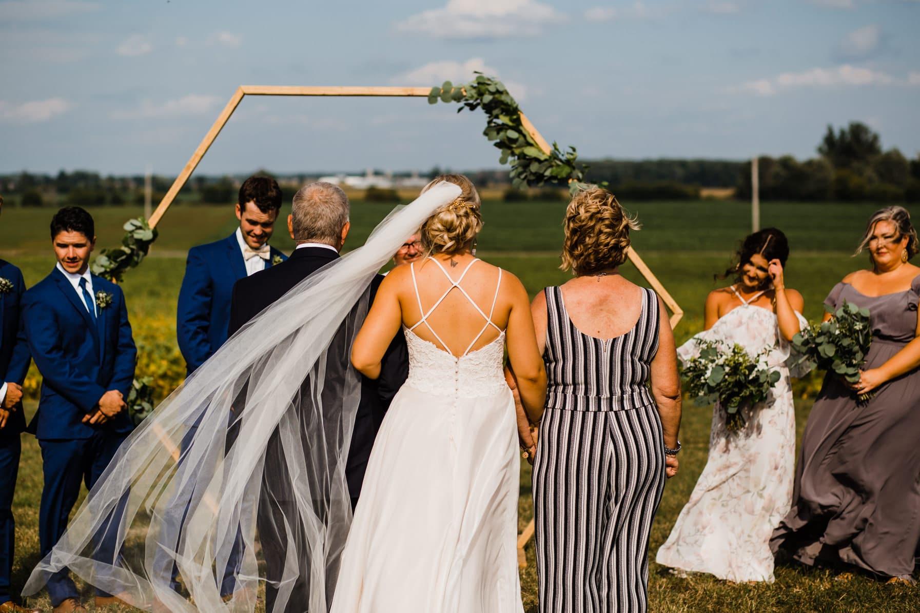 bride walks down aisle with mom and dad - summer farm wedding