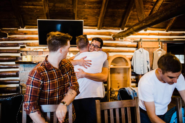 groom and groomsman hug summer camp wedding