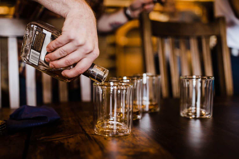 groomsman pours whiskey summer camp wedding