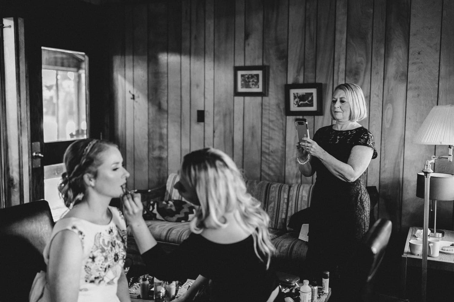 bride's mother takes photo of bride summer camp wedding