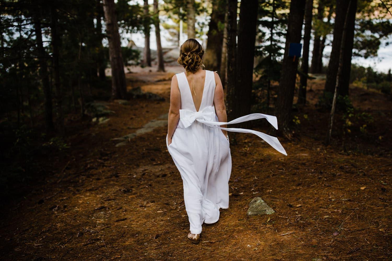 bride walks through forest to first look summer camp wedding