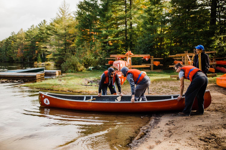 summer camp wedding - groom and groomsmen go for canoe ride