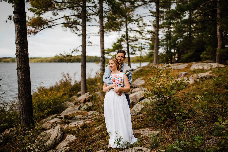 bride and groom by water at bark lake wedding