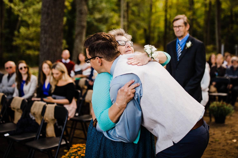groom hugs mother at summer camp wedding
