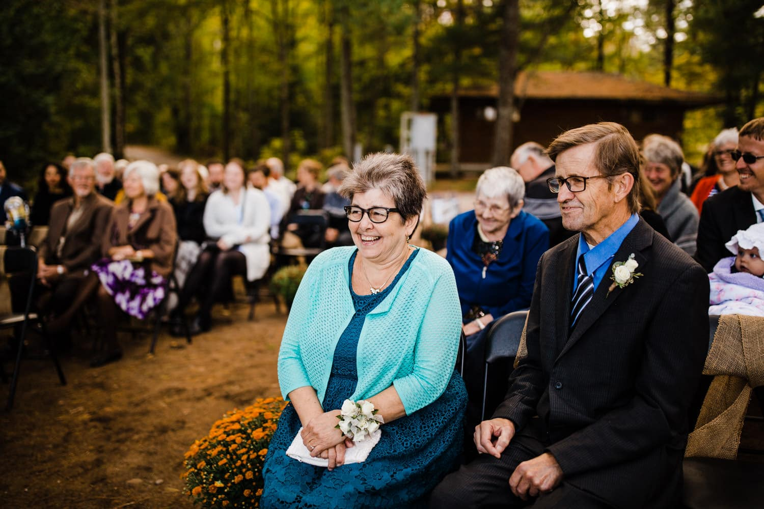 groom's parents laugh during wedding ceremony