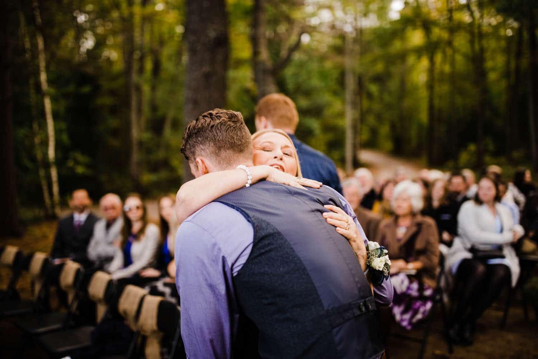 bride's mother hugs son at summer camp wedding