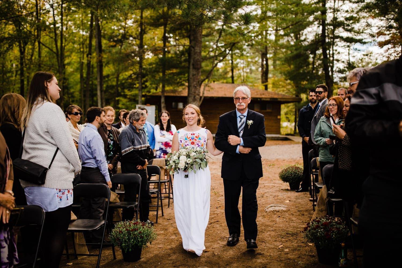 bride walks down aisle with dad - summer camp wedding