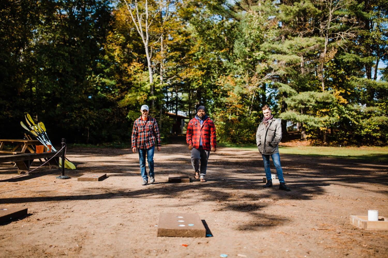 groomsmen play lawn games at summer camp wedding