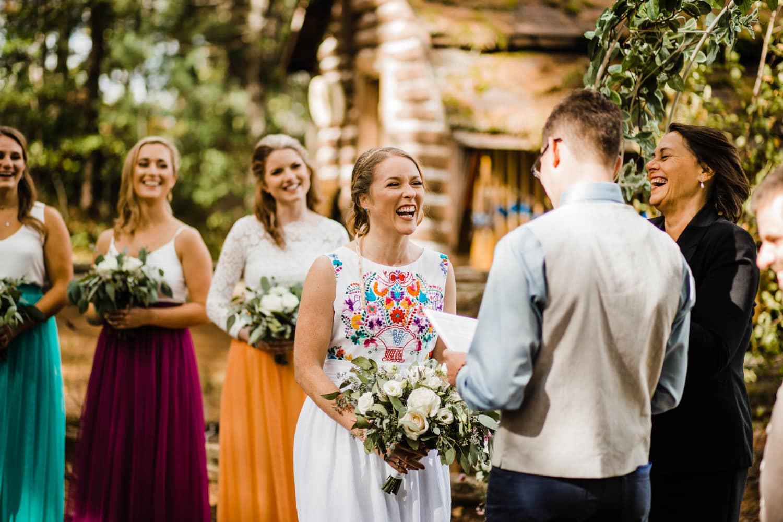 bride laughs during vows at bark lake summer camp wedding