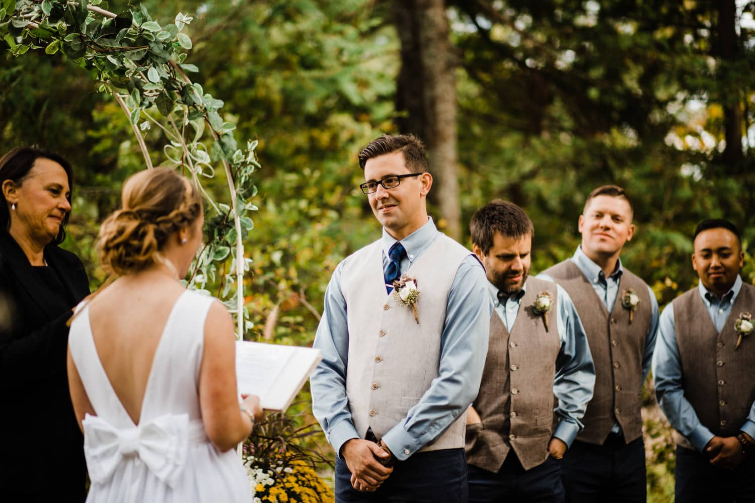 groom listens to vows at summer camp wedding