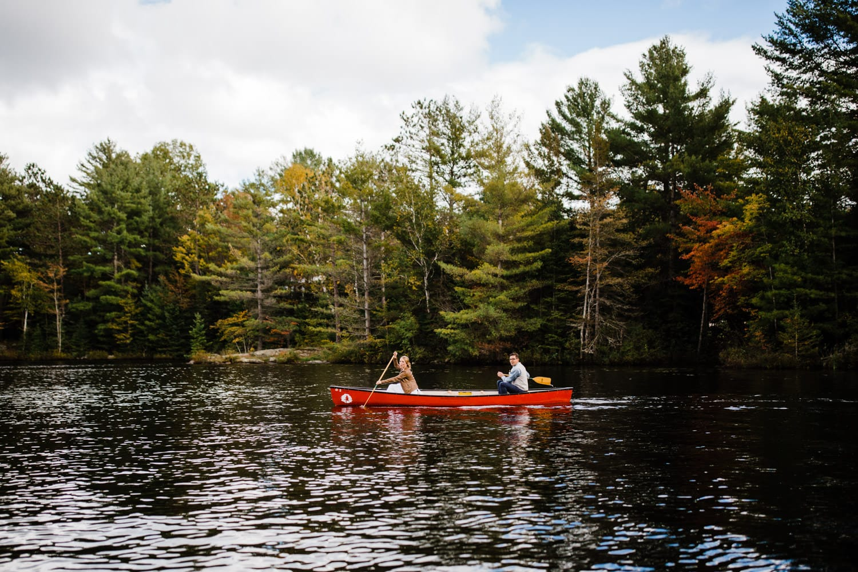 bride and groom go for canoe ride - bark lake summer camp wedding